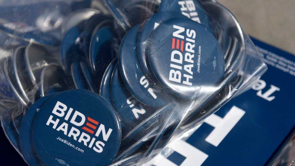 Biden/Harris pins are displayed by the Joe Biden campaign are seen on a table at an early voting satellite location at the Anne B. Day elementary school, Thursday, Oct. 15, 2020, in Philadelphia.