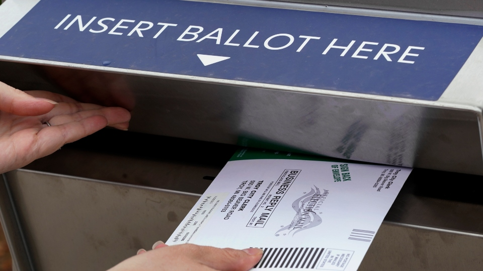 In this Thursday, Oct. 15, 2020, file photo, Nikki Schueller inserts her absentee voter ballot into a drop box in Troy, Mich.