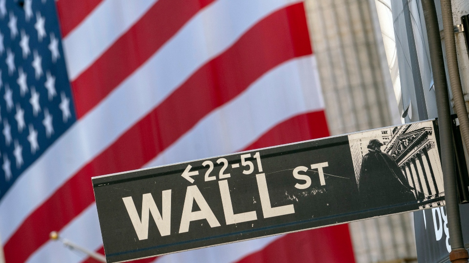 In this Monday, Sept. 21, 2020, file photo, a Wall Street street sign is framed by a giant American flag hanging on the New York Stock Exchange in New York.