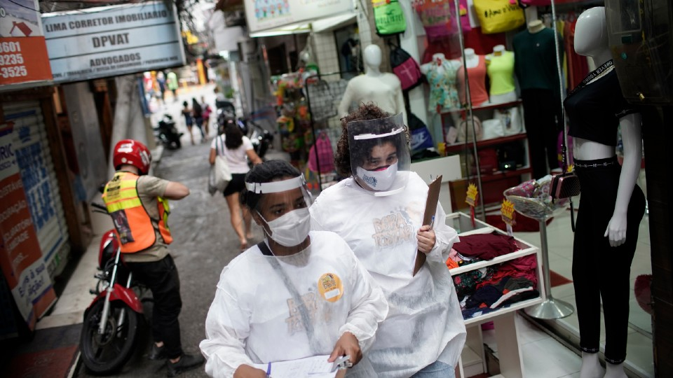 Health workers walk through the Rocinha slum in Brazil