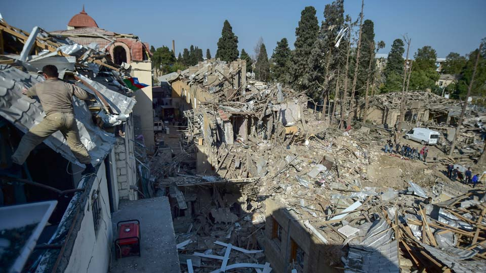 People look at the destroyed houses a day after shelling by Armenian's artillery during fighting over the separatist region of Nagorno-Karabakh, in Ganja, Azerbaijan, Monday, Oct. 12, 2020