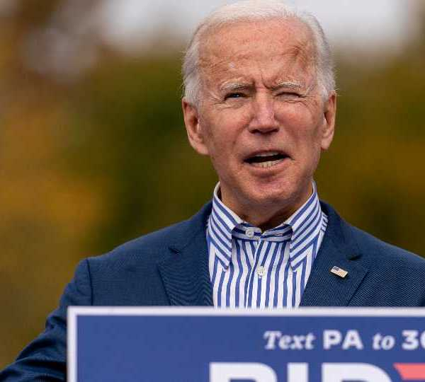 Democratic presidential candidate former Vice President Joe Biden holds up his daily schedule which has a daily update on US Troop deaths and wounded numbers as he speaks at a drive-in campaign stop at Bucks County Community College in Bristol, Pa., Saturday, Oct. 24, 2020.