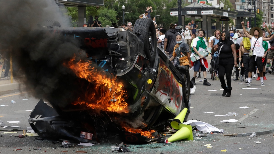 In this May 30, 2020, file photo, protesters demonstrate as a Salt Lake City police vehicle burns, in Salt Lake City.