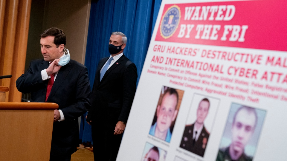 A poster showing six wanted Russian military intelligence officers is displayed as Assistant Attorney General for the National Security Division John Demers, left, takes the podium to speak at a news conference at the Department of Justice, Monday, Oct. 19, 2020, in Washington.