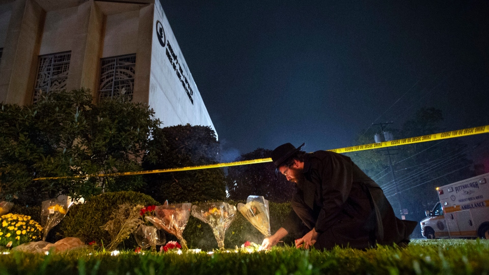 In this Oct. 27, 2018 photo, Rabbi Eli Wilansky lights a candle after a mass shooting at Tree of Life Synagogue in Pittsburgh's Squirrel Hill neighborhood.