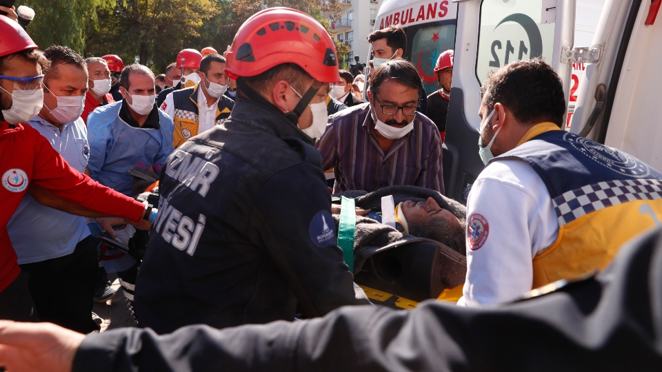 Medics and rescue personnel carry into an ambulance an injured person from the debris of a collapsed building in Izmir, Turkey, Saturday, Oct. 31, 2020. Rescue teams on Saturday ploughed through concrete blocs and debris of eight collapsed buildings in Turkey's third largest city in search of survivors of a powerful earthquake that struck Turkey's Aegean coast and north of the Greek island of Samos, killing dozens Hundreds of others were injured.