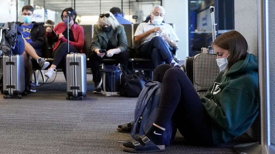 In this Oct. 15, 2020, file photo, passenger Cari Driggs, right, from Provo, Utah, waits to board a United Airlines flight to Hawaii for vacation at San Francisco International Airport in San Francisco.