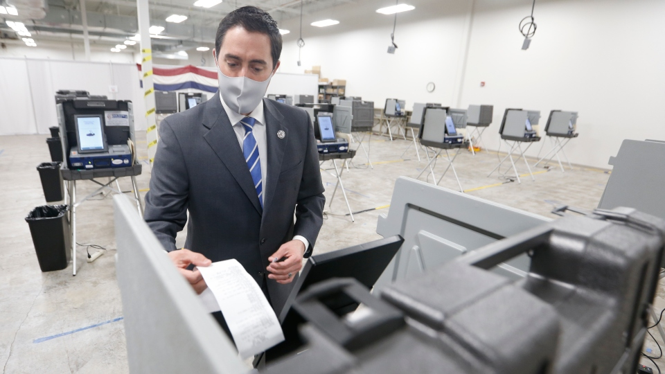 Ohio Secretary of State Frank LaRose demonstrates receiving a printed ballot receipt during a media tour of the Delaware County Board of Elections in Delaware, Ohio, Sunday, Nov. 1, 2020.