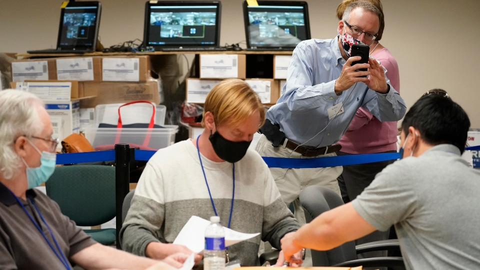 Republican canvas observer Ed White, takes photos with his smart phone as Lehigh County workers count ballots as vote counting in the general election continues, Friday, Nov. 6, 2020, in Allentown, Pa.