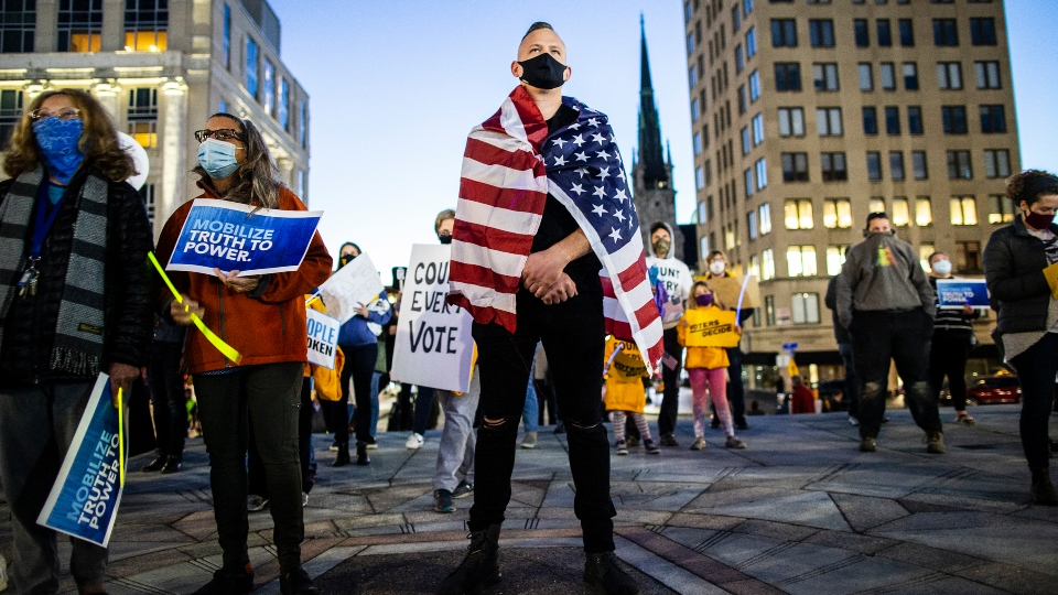 """Mitchel Bauer, of Harrisburg, stands during a """"Rally to Count Every Vote,"""" on the Capitol steps in Harrisburg, Pa., Wednesday, Nov. 4, 2020."""