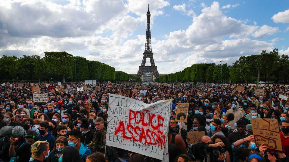 "In this June 6, 2020 file photo, hundreds of demonstrators gather near the Eiffel Tower, some with a banner reading ""Police, murderers"" during a demonstration in Paris, France, to protest against the recent killing of George Floyd, a Black man who died in police custody in Minneapolis, U.S.A. As videos helped reveal many cases of police brutality, French civil rights activists voiced fears that a new security law would threaten efforts by people from minorities and poor neighborhoods to document incidents involving law enforcement officers. French President Emmanuel Macron's government is pushing a new security bill that would notably make it illegal to publish images of officers with intent to cause them harm."