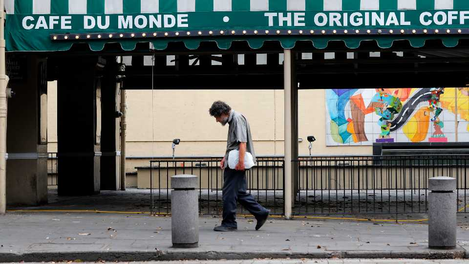 FILE - In this March 27, 2020, file photo, a man walks past the Cafe Du Monde restaurant, which was closed but has since reopened, in the French Quarter of New Orleans. President-elect Joe Biden will inherit a mangled U.S. economy, one that never fully healed from the coronavirus and could suffer again as new infections are climbing. The once robust recovery has shown signs of gasping after federal aid lapsed. Ten million remain jobless and more layoffs are becoming permanent. The Federal Reserve found that factory output dropped.