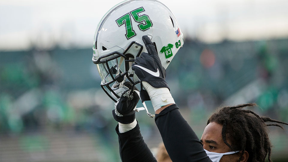 "Marshall player holds helmet with ""75"" decal"