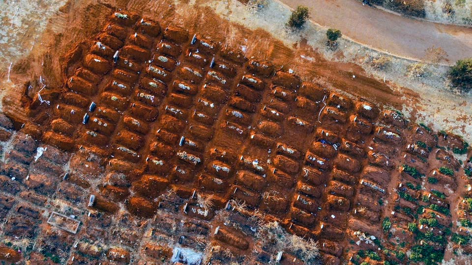 Recently filled graves are seen in the Olifantsveil Cemetery outside Johannesburg, South Africa