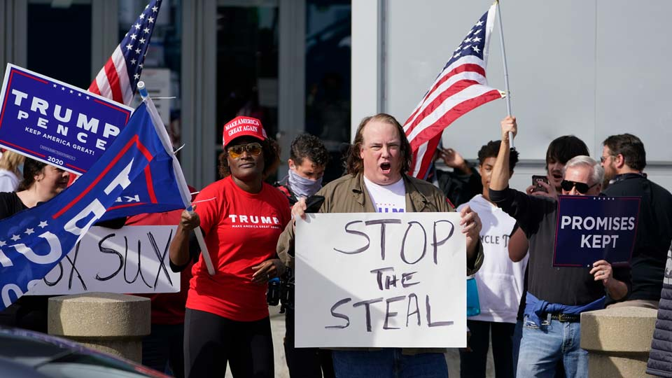 Supports of President Donald Trump holds signs during a demonstration outside the State Farm Arena where Fulton County has a voting counting operation, Thursday, Nov. 5, 2020