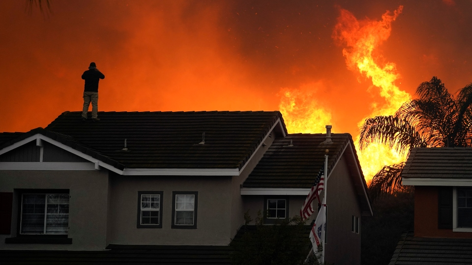 In this Tuesday, Oct. 27, 2020 file photo, Herman Termeer, 54, stands on the roof of his home as the Blue Ridge Fire burns along the hillside in Chino Hills, Calif.