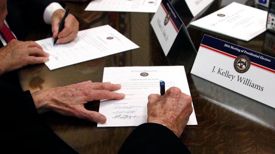 In this Dec. 19, 2016, file photo members of the Mississippi Electoral College sign certificates of vote in the process of formally casting their electoral votes in the 2016 General Election
