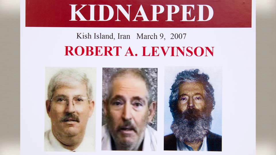 In this March 6, 2012, file photo, an FBI poster showing a composite image of former FBI agent Robert Levinson, right, of how he would look like now after five years in captivity, and an image, center, taken from the video, released by his kidnappers, and a picture before he was kidnapped, left, displayed during a news conference in Washington.