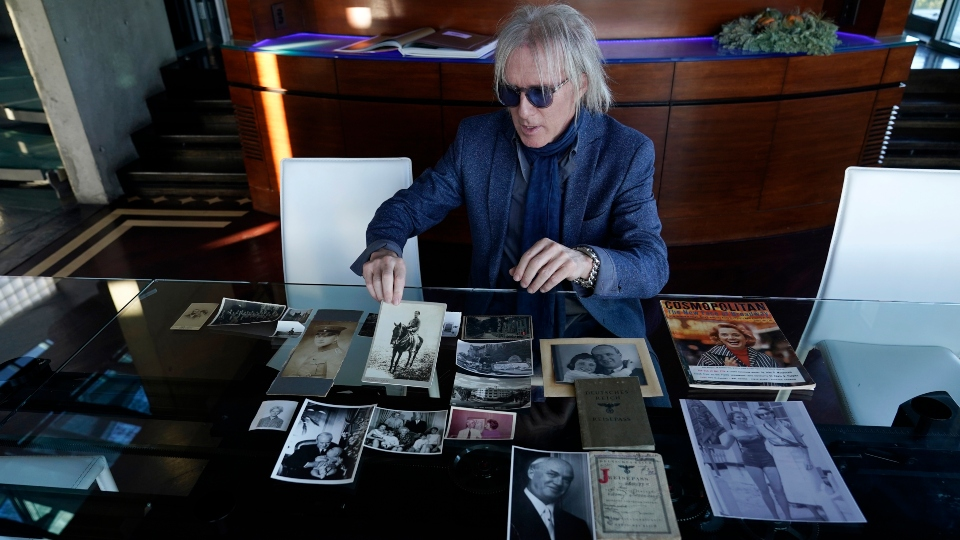 Jed Leiber shows photos of his grandfather Saemy Rosenberg's life at home Thursday, Dec. 3, 2020, in Los Angeles.