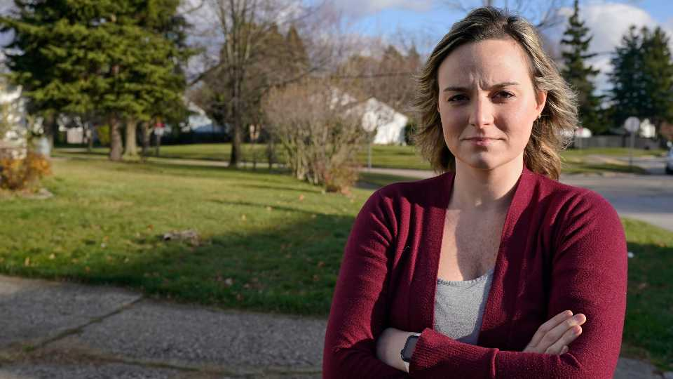 Ashley Hagstrom poses outside her house, Monday, Nov. 23, 2020, in Parma, Ohio. The state's efforts to recoup unemployment compensation it mistakenly paid during the pandemic is causing new headaches for some laid-off Ohioans still awaiting money they are legitimately due. The state made about $48 million in overpayments during the first six months of the coronavirus outbreak, and has recouped about half that amount. Hagstrom was a caterer for the Cleveland Browns who was furloughed in early April. The state mistakenly paid her during her maternity leave and demanded repayment while still not paying her the unemployment wages she's owed.