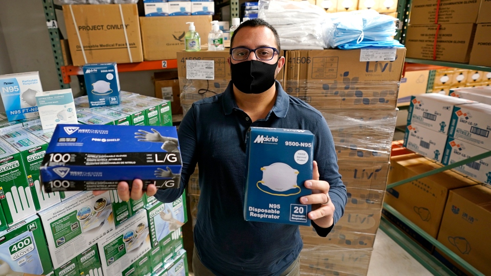 Ray Bellia holds up personal protective masks and gloves, used by medical and law enforcement professionals, in the warehouse of his Body Armor Outlet store, Wednesday, Dec. 9, 2020, in Salem, N.H. Bellia's store rapidly evolved into one of the nation's 20 largest suppliers of personal protective equipment to states this past spring, according to a nationwide analysis of state purchasing data by The Associated Press.
