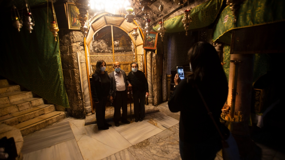 Christians take photos inside the Grotto of the Church of the Nativity, traditionally believed to be the birthplace of Jesus Christ, in the West Bank city of Bethlehem, Monday, Nov. 23, 2020.