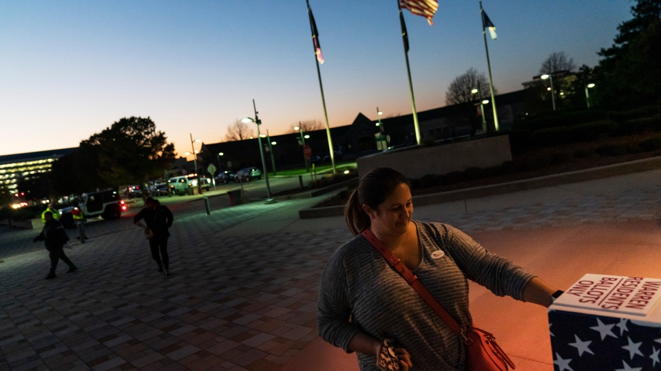 In this Tuesday, Nov. 3, 2020 file photo, Wendy Gill inserts her absentee ballot at a drop-off box as the sun sets on Election Day outside City Hall in Warren, Mich.
