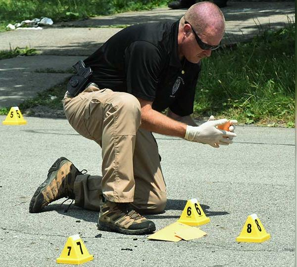 Youngstown police officer Greg Miller collects shell casings July 8 after a shooting on North Hazelwood Avenue injured two people. Police have dealt with an uptick in shootings this year and police Chief Robin Lees says much of that crime is driven by people who are not allowed to own guns.