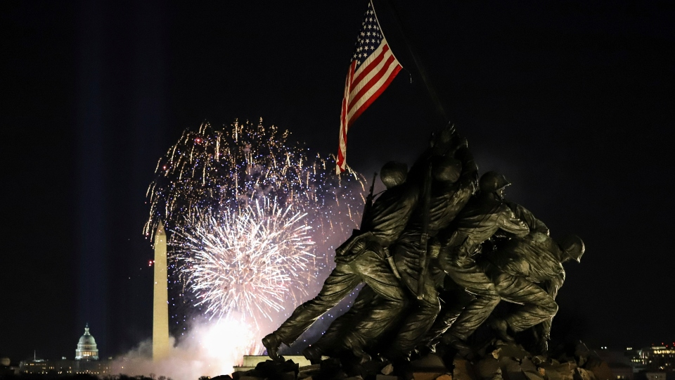 Fireworks explode over the Washington Monument with the Marine Corps War Memorial in the foreground, Wednesday, Jan. 20, 2021, in Arlington, Va.