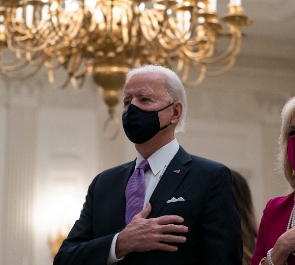 President Joe Biden, accompanied by first lady Jill Biden, places his hand over his heart during a performance of the national anthem, during a virtual Presidential Inaugural Prayer Service in the State Dinning Room of the White House, Thursday, Jan. 21, 2021, in Washington.