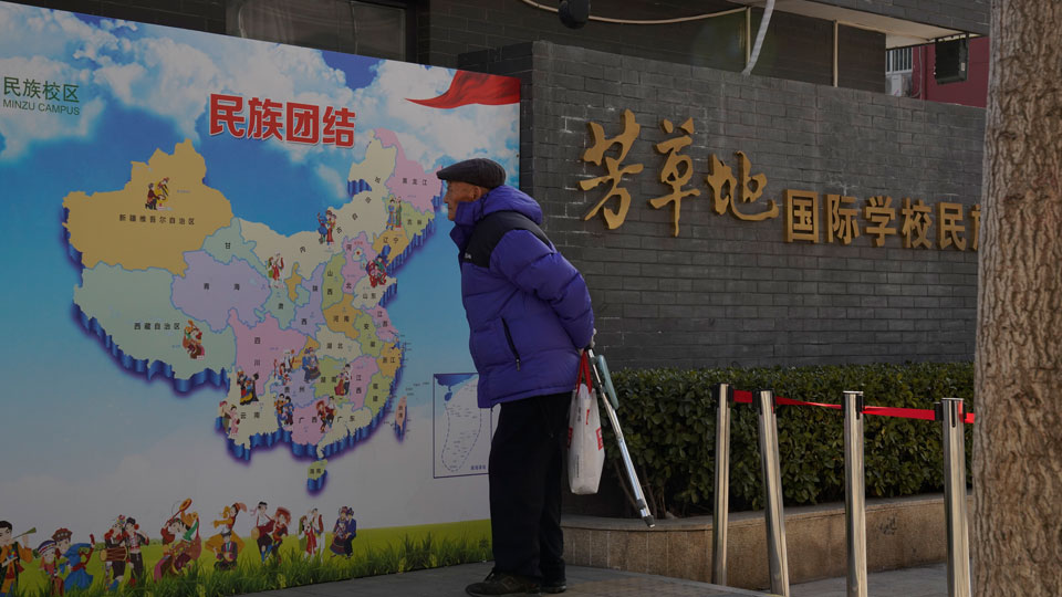 """An elderly Chinese man looks at map of Chinese showing its different ethnic groups and the slogan """"Ethnic Unity"""" in Beijing, China Monday, Jan. 11, 2021"""