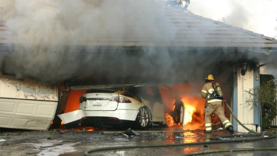 This undated photo provided by National Transportation Safety Board, The Orange County Fire Authority battles a fire on a burning vehicle inside a garage in Orange County, Calif.