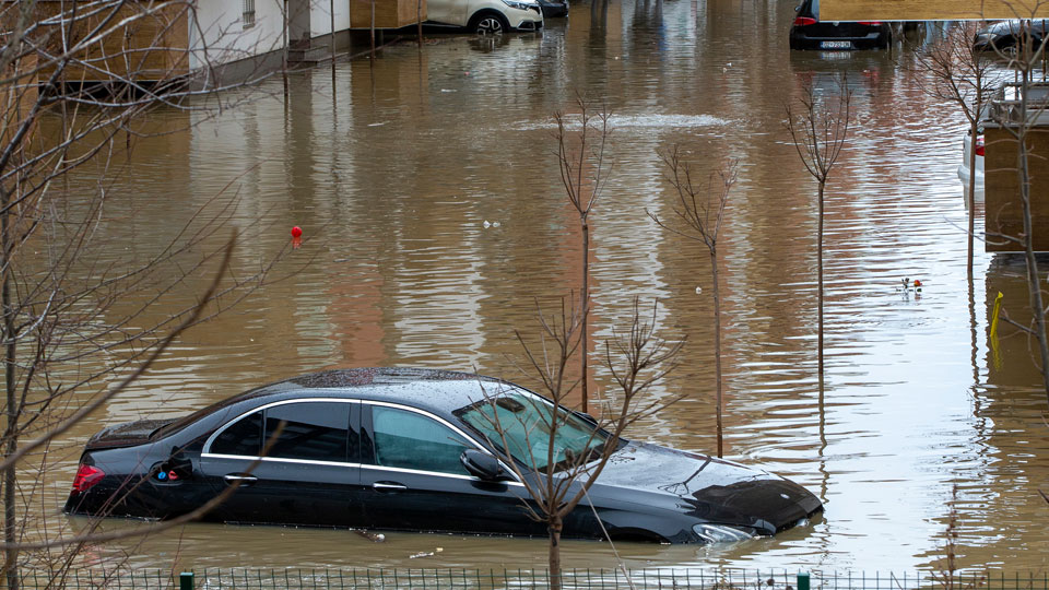 Stranded residents try to reach their cars in the flooded street, following heavy rain and snowfall in Fushe Kosove, Kosovo on Monday, Jan. 11, 2021