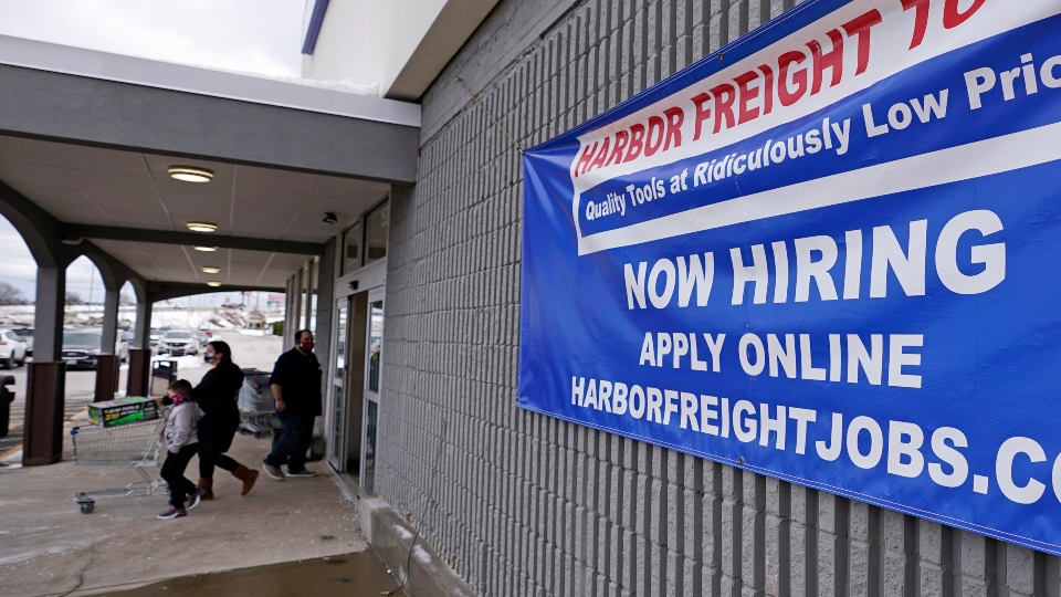"""In this Dec. 10, 2020, file photo, a """"Now Hiring"""" sign hangs on the front wall of a Harbor Freight Tools store in Manchester, N.H."""