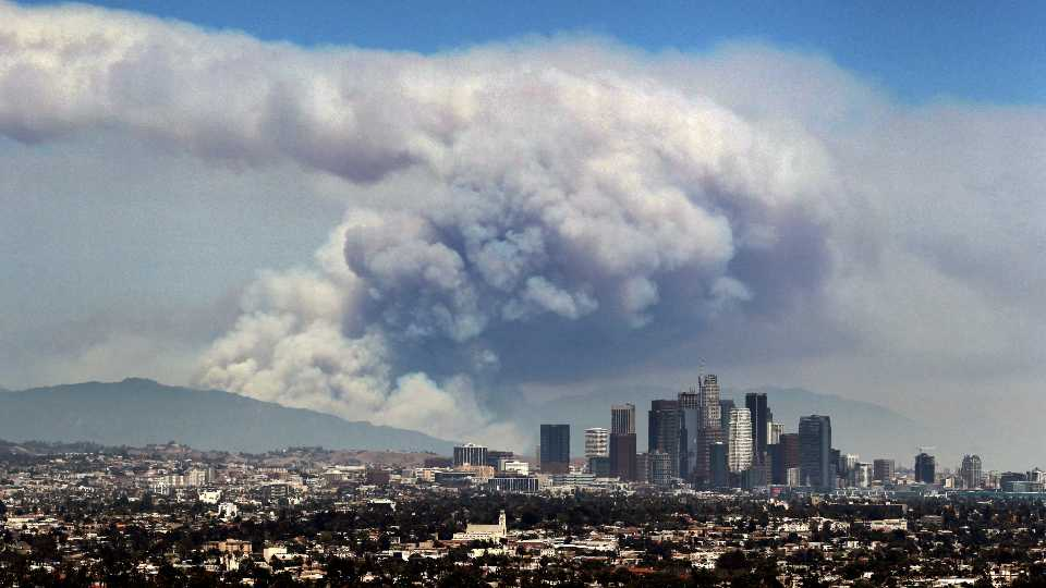FILE - In this Monday, June 20, 2016 file photo, smoke from wildfires burning in Angeles National Forest fills the sky behind the Los Angeles skyline. The Federal Emergency Management Agency has calculated the risk for every county in America for 18 types of natural disasters, such as earthquakes, hurricanes, tornadoes, floods, volcanos and even tsunamis. And of the more than 3,000 counties, Los Angeles County has the highest ranking in the National Risk Index.