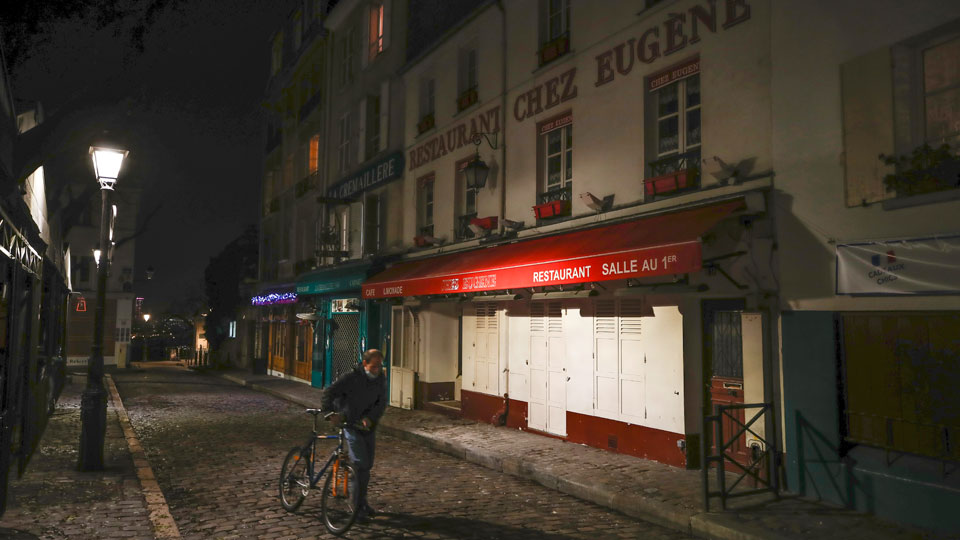 Man pushes his bicycle along a row of closed restaurants