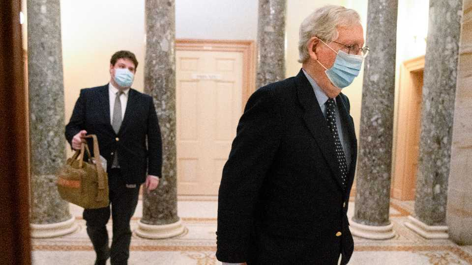 Followed by a staffer holding a bag, Senate Majority Leader Mitch McConnell of Ky., right, leaves the Capitol for the day, Tuesday, Dec. 29, 2020, on Capitol Hill in Washington.