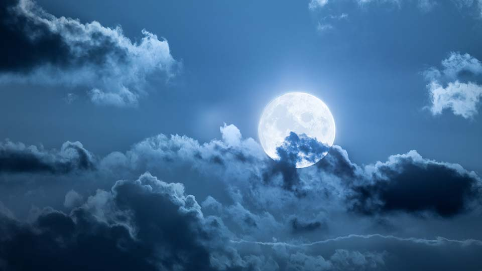 The moon in the cloudy night sky.