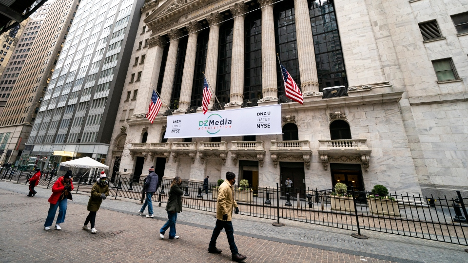 Pedestrians pass the New York Stock Exchange, Wednesday, Jan. 27, 2021, in New York. Major indexes opened lower on Wall Street Friday, Jan. 29, while shares of GameStop, AMC and several other stocks being targeted by a rowdy community of amateur investors soared again.