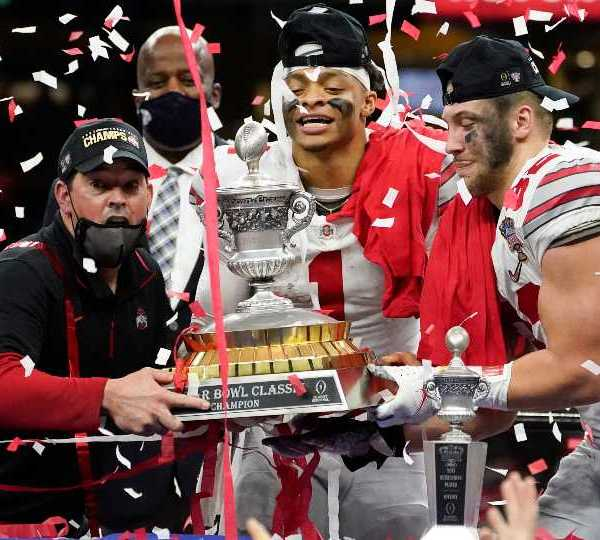 Ohio State head coach Ryan Day, from left, quarterback Justin Fields and linebacker Tuf Borland hold up the trophy after the team's win against Clemson in the Sugar Bowl NCAA college football game Friday, Jan. 1, 2021, in New Orleans. Ohio State won 49-28.