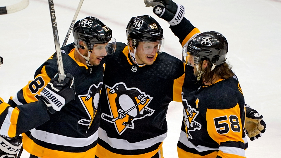 Pittsburgh Penguins' Jake Guentzel (59) celebrates after scoring with Sidney Crosby (87) and Kris Letang during the third period of an NHL hockey game against the New York Rangers in Pittsburgh, Sunday, Jan. 24, 2021. The Penguins won 3-2.
