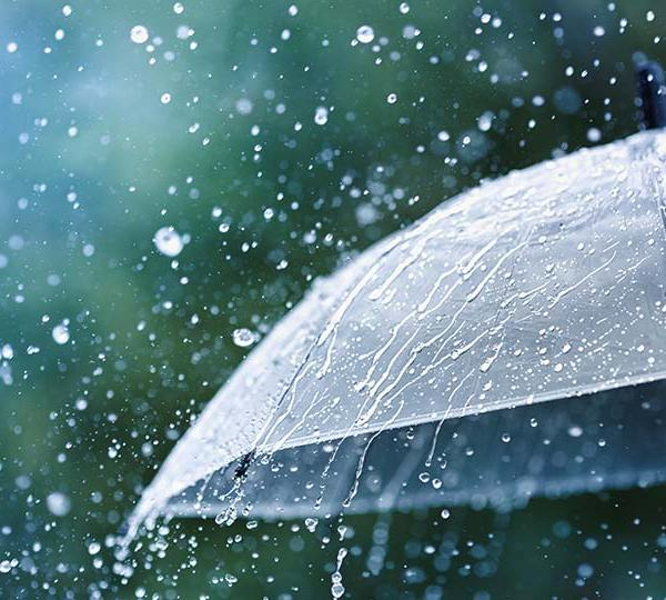 Rain drops falling on an umbrella during a storm.