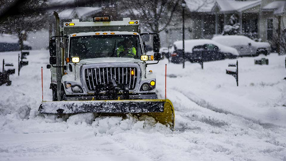 A snow plow clearing a road during winter.