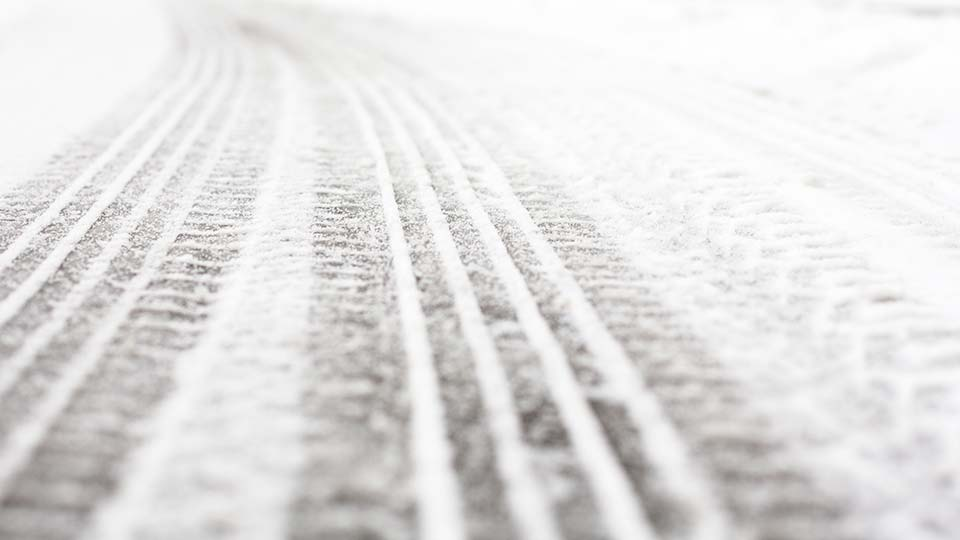 Tire tracks in the snow on a road during winter.