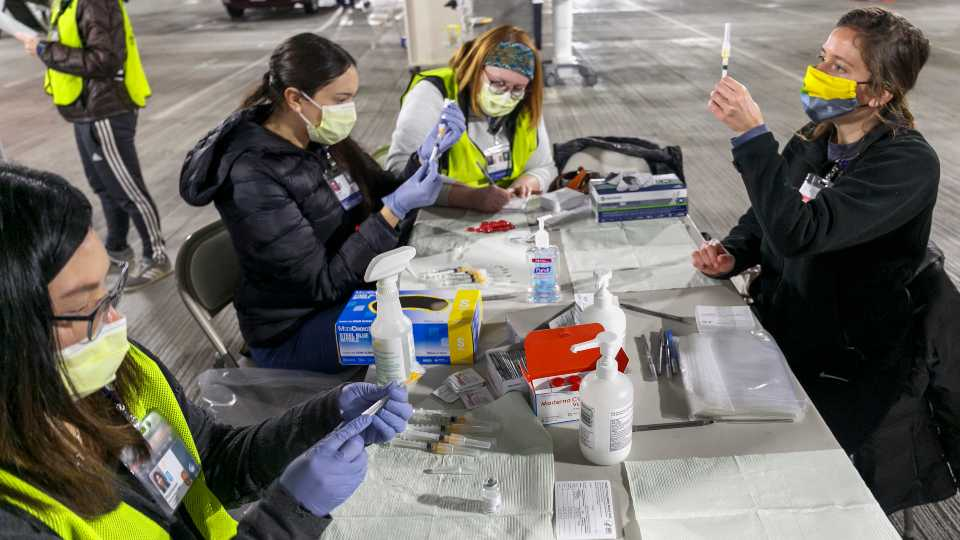 In this Sunday, Jan. 10, 2021, file photo, Medical professionals from Oregon Health & Science University load syringes with the Moderna COVID-19 vaccine at a drive-thru vaccination clinic in Portland, Ore. The U.S. is entering the second month of the largest vaccination effort in history with a massive expansion of the campaign, opening up football stadiums, major league ballparks, fairgrounds and convention centers to inoculate a larger and more diverse pool of people.