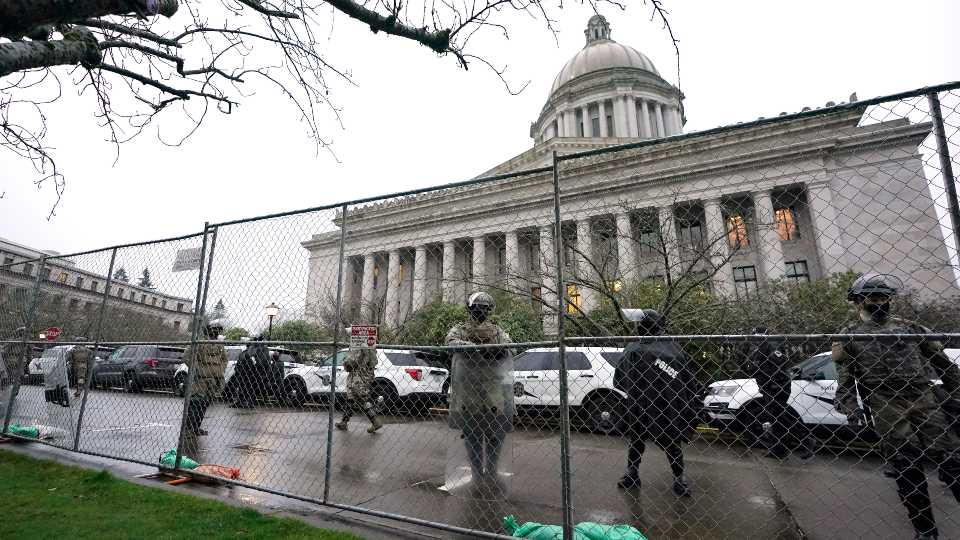 Members of the Washington National Guard stand near a fence surrounding the Capitol in anticipation of protests Monday, Jan. 11, 2021, in Olympia, Wash. State capitols across the country are under heightened security after the siege of the U.S. Capitol last week.