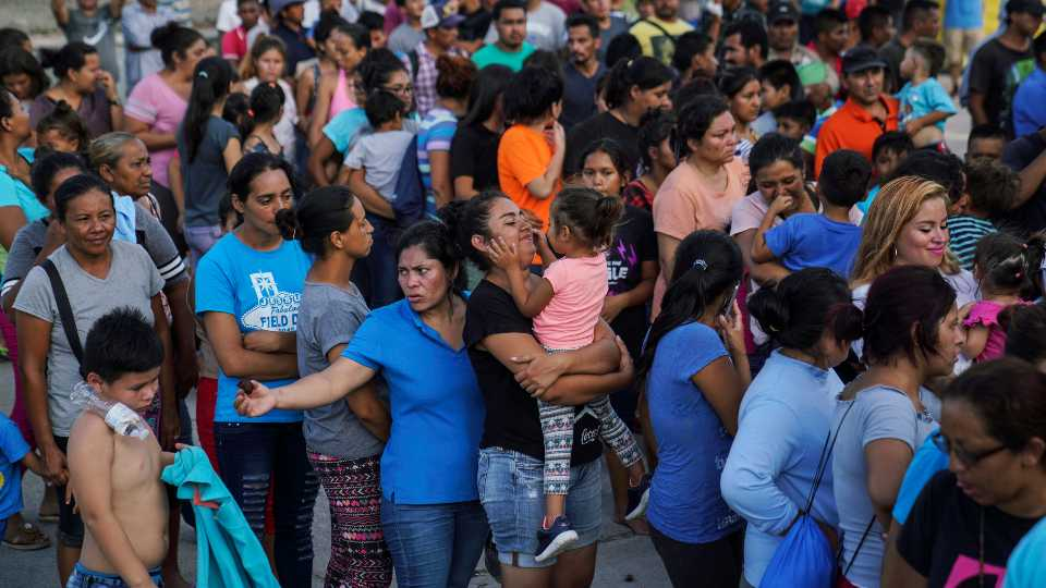 """FILE - In this Aug. 30, 2019, file photo, migrants, many of whom were returned to Mexico under the Trump administration's """"Remain in Mexico"""" policy, wait in line to get a meal in an encampment near the Gateway International Bridge in Matamoros, Mexio. The Biden administration on Friday, Feb. 12, 2021, announced plans for tens of thousands of asylum-seekers waiting in Mexico for their next immigration court hearings to be released in the United States while their cases proceed"""
