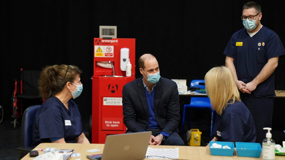 Britain's Prince William, center, speaks to staff and volunteers during his visit to the King's Lynn Corn Exchange Vaccination Centre in King's Lynn, Monday Feb. 22, 2021.