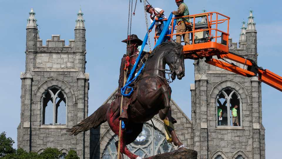 FILE - In this July 7, 2020, file photo, crews attach straps to the statue Confederate General J.E.B. Stuart on Monument Avenue in Richmond, Va. At least 160 Confederate symbols were taken down or moved from public spaces in 2020. That's according to a new count the Southern Poverty Law Center shared with The Associated Press.