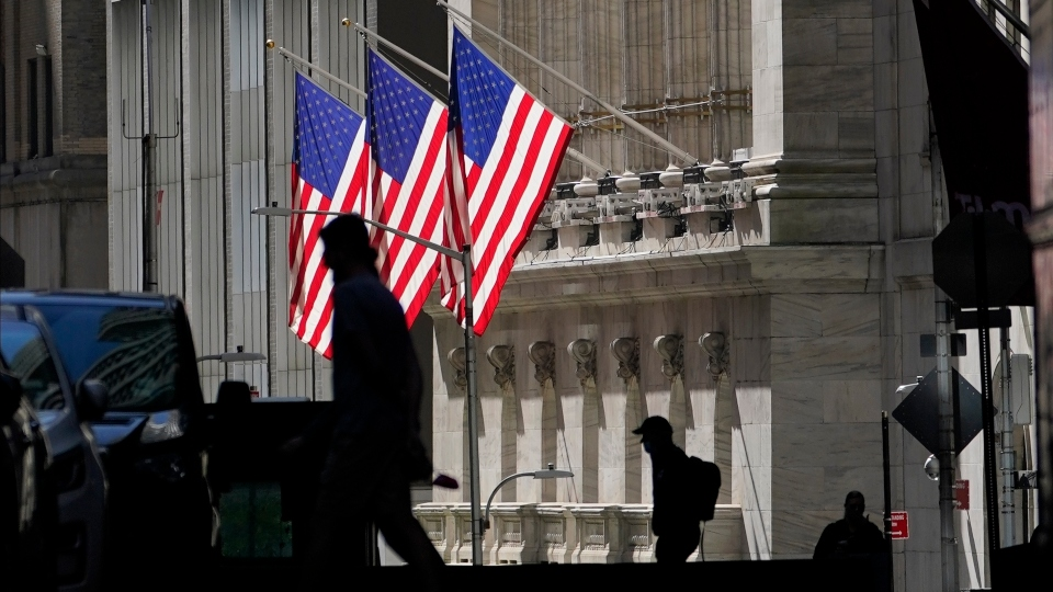 In this Oct. 14, 2020 file photo, pedestrians pass the New York Stock Exchange in New York.
